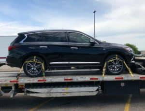 Infinity JX35 strapped to transport trailer in parkling lot
