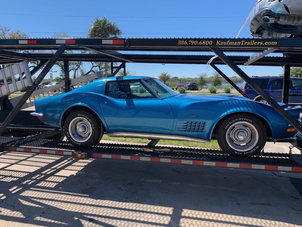 bright blue vintage corvette on trailer for auto transport