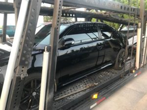all black sedan being hauled on multi car trailer, one of the advantages of using an auto transport company