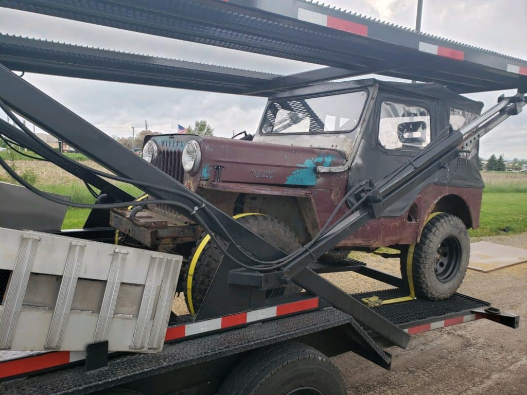 vintage jeep on stepdeck trailer for auto transport