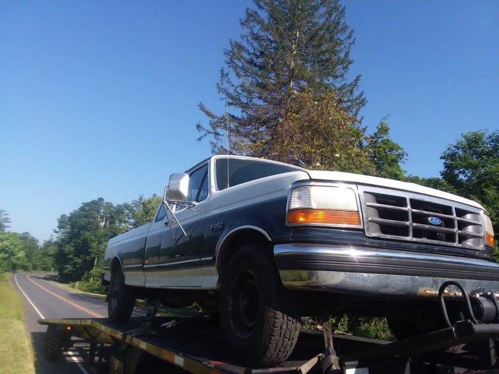 old school f250 on trailer for auto transport