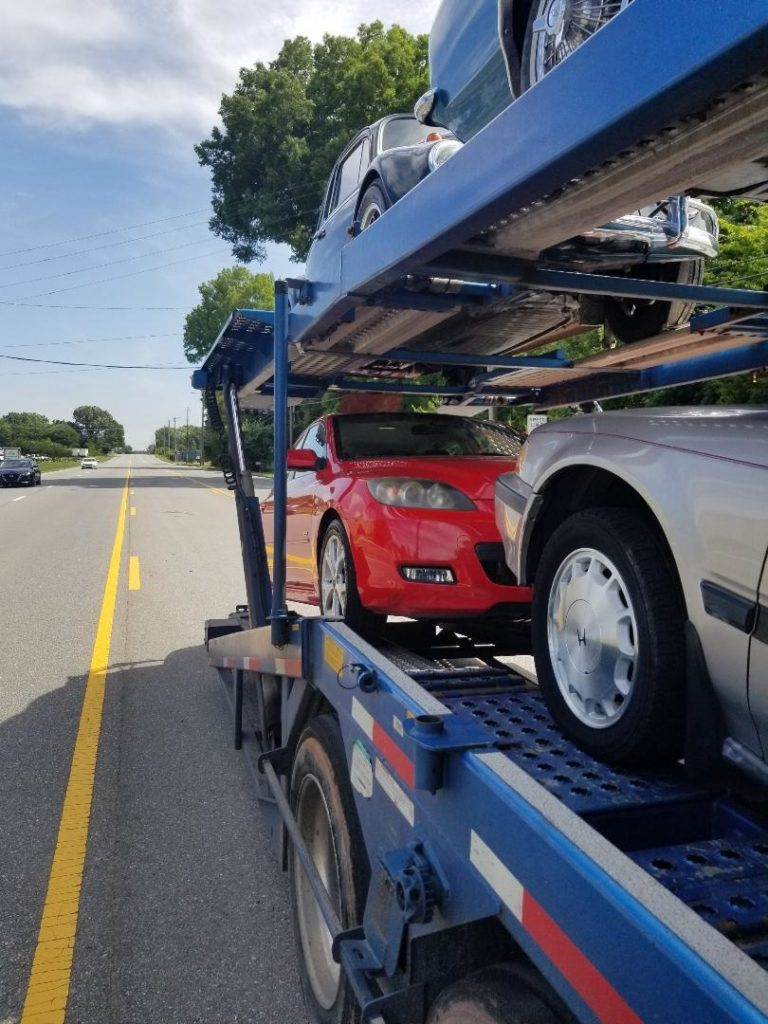 multiple cars on car transport carrier on the open road