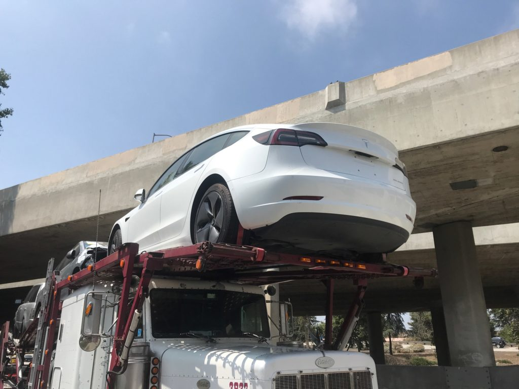 white tesla on vehicle trailer for auto transport