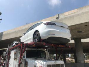 white tesla on vehicle trailer for auto transport