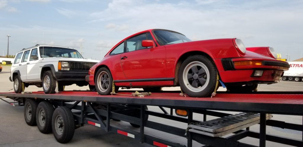 vintage red porsche 911 on diagonal trailer for auto transport