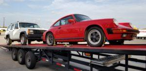 vintage red porsche 911 on diagonal trailer for auto transport