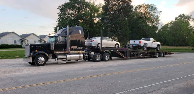 two vehicles back to back on stepdeck trailer for auto transport