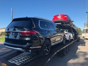 black bmw beig loaded onto trailer for transport shows the advantages of using an auto transport company