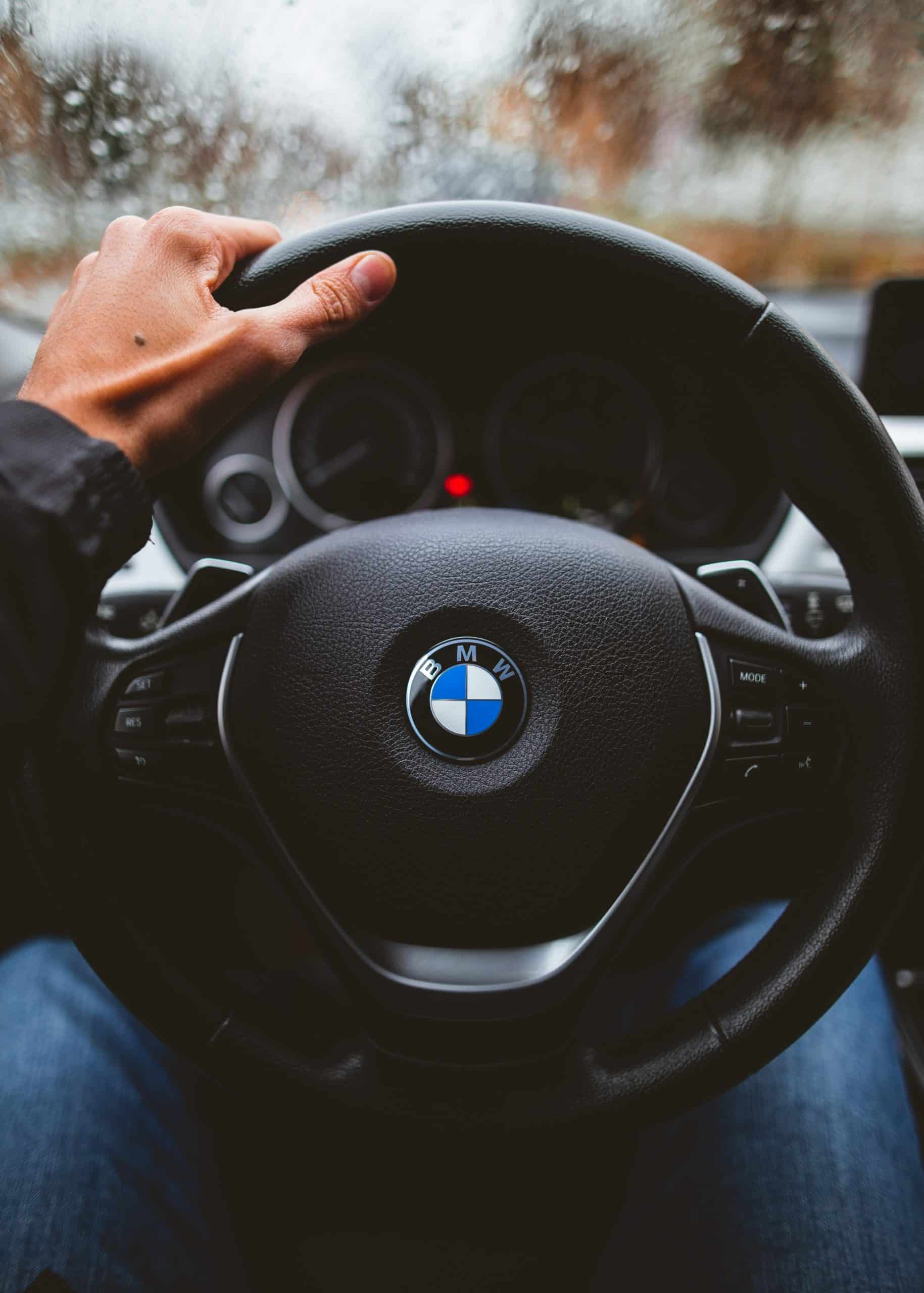 BMW steering wheel with male hand on upper left side