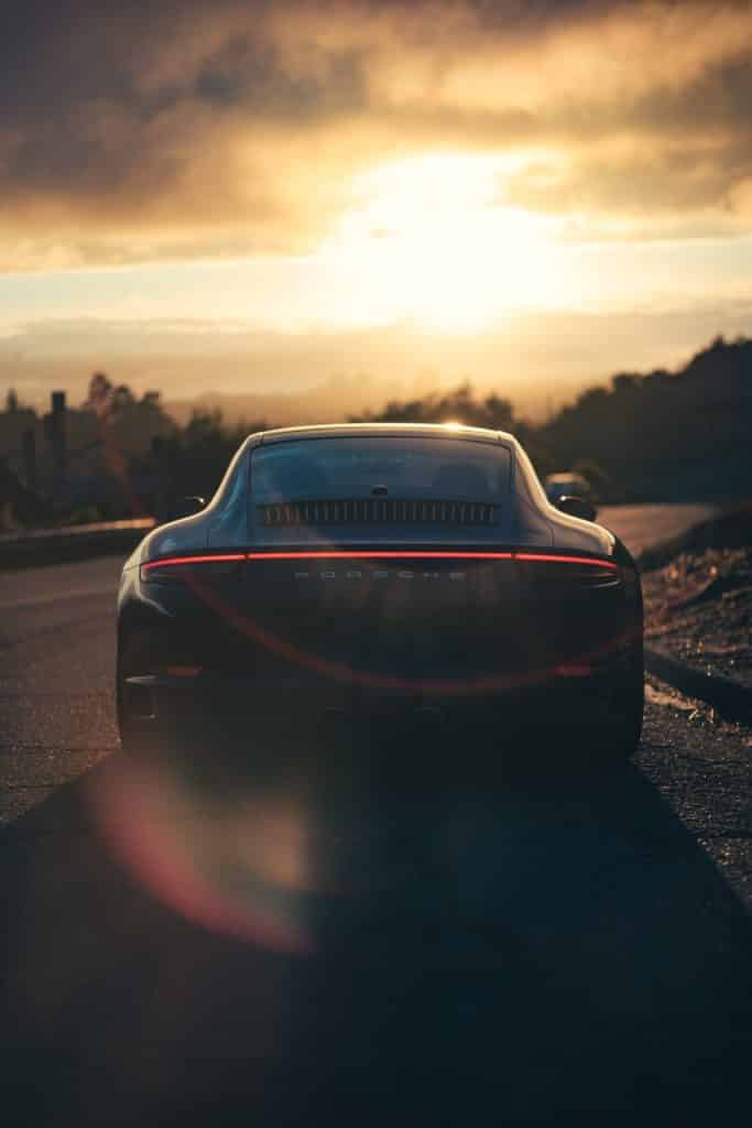 porsche 911 with red stripe lights infront of beautiful sunset