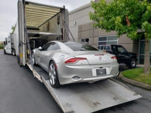 silver fisker karma going into elevated trailer for auto transport