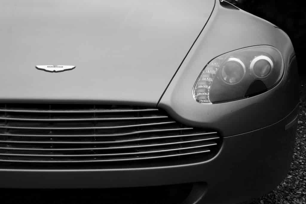 faded gray aston martin vantage on black pebble road