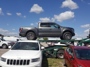 silver raptor truck on trailer for auto transport