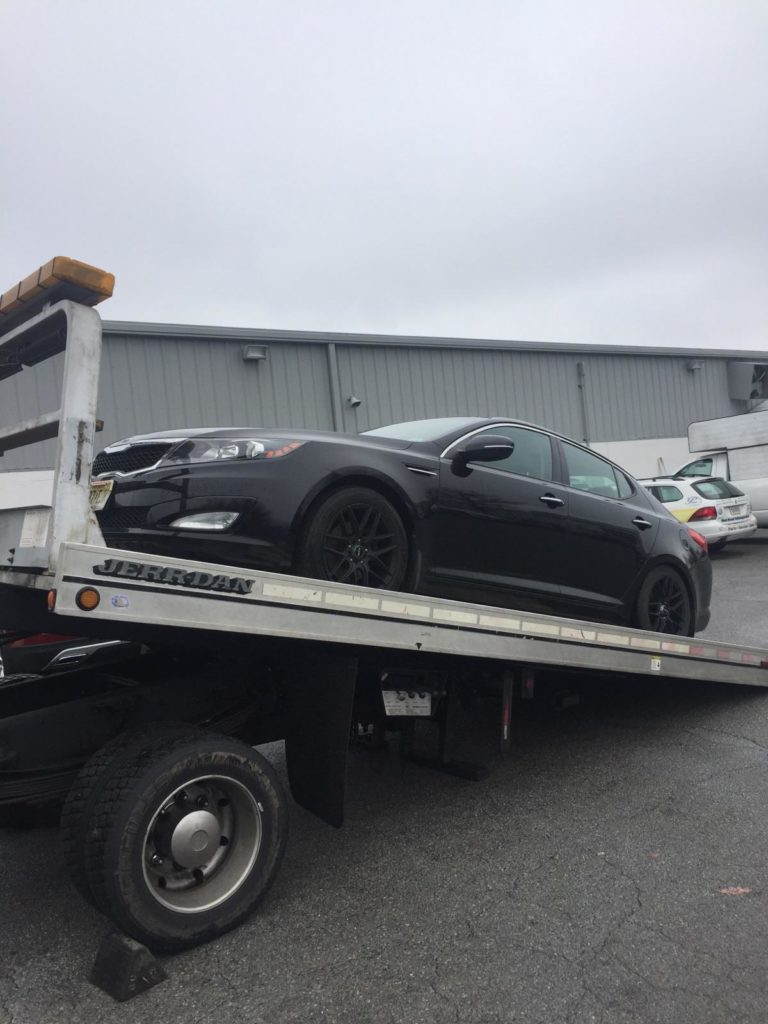 black kia on rng trailer for auto transport