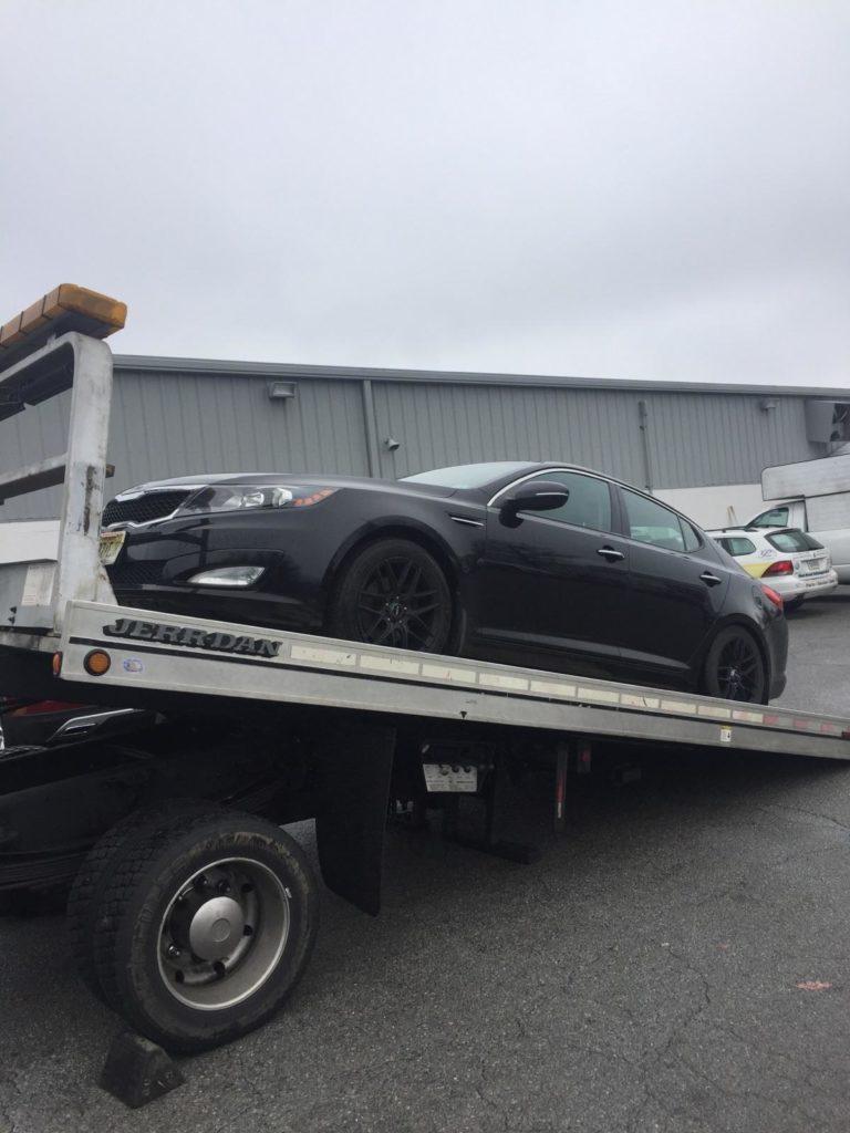 black hyundai car on top of logistics ramp