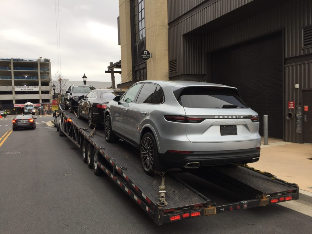 silver porsche suv on trailer for auto transport