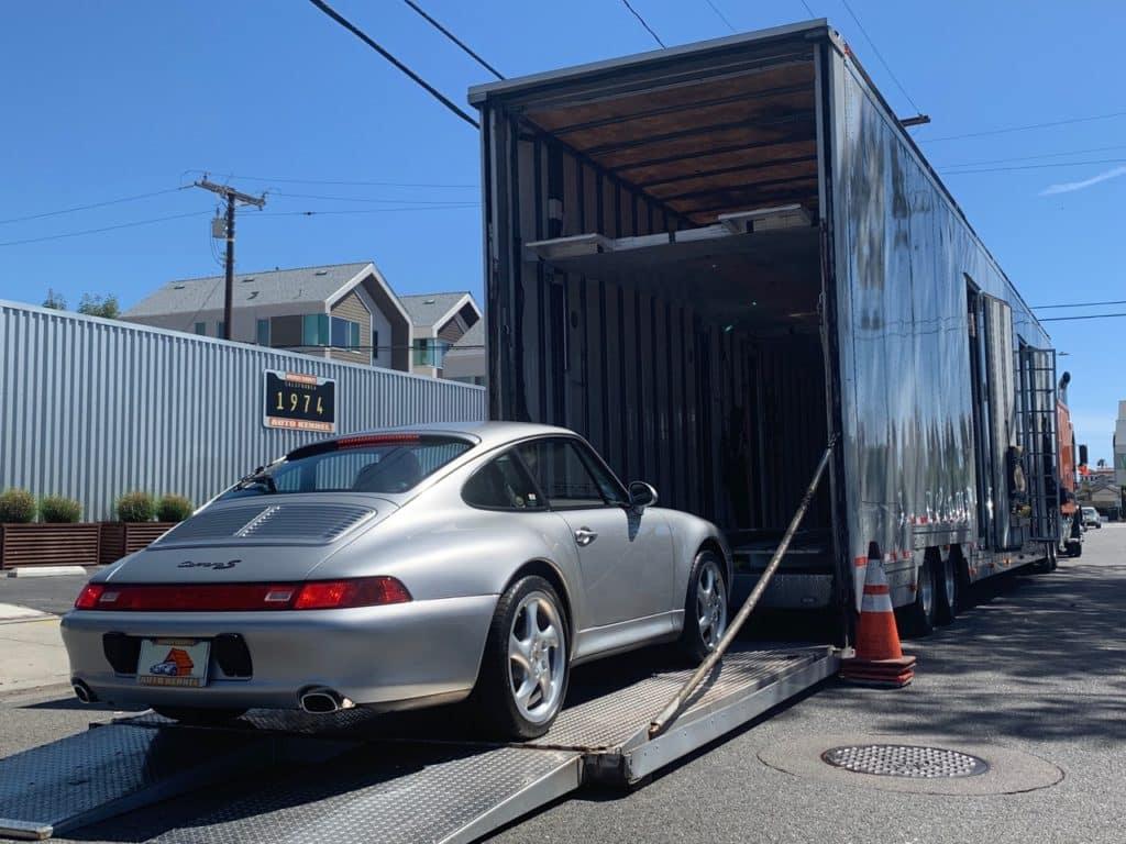 silver carrera porsche in enclosed trailer for auto transport
