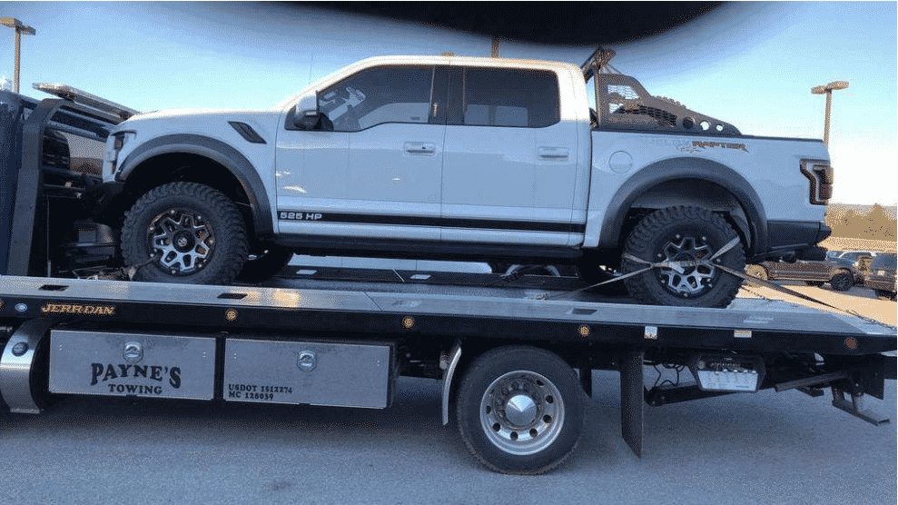 white ford raptor truck on car shipping trailer