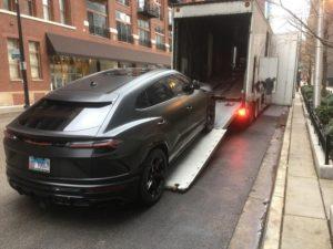 black lamborgini suv loading into enclosed transport trailer on busy street