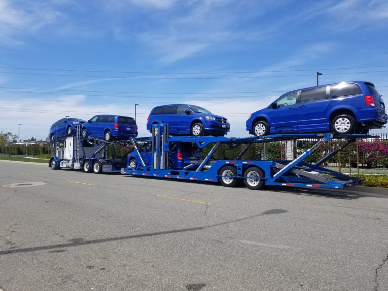 Four blue mobility vans on auto transport trailers on concrete road