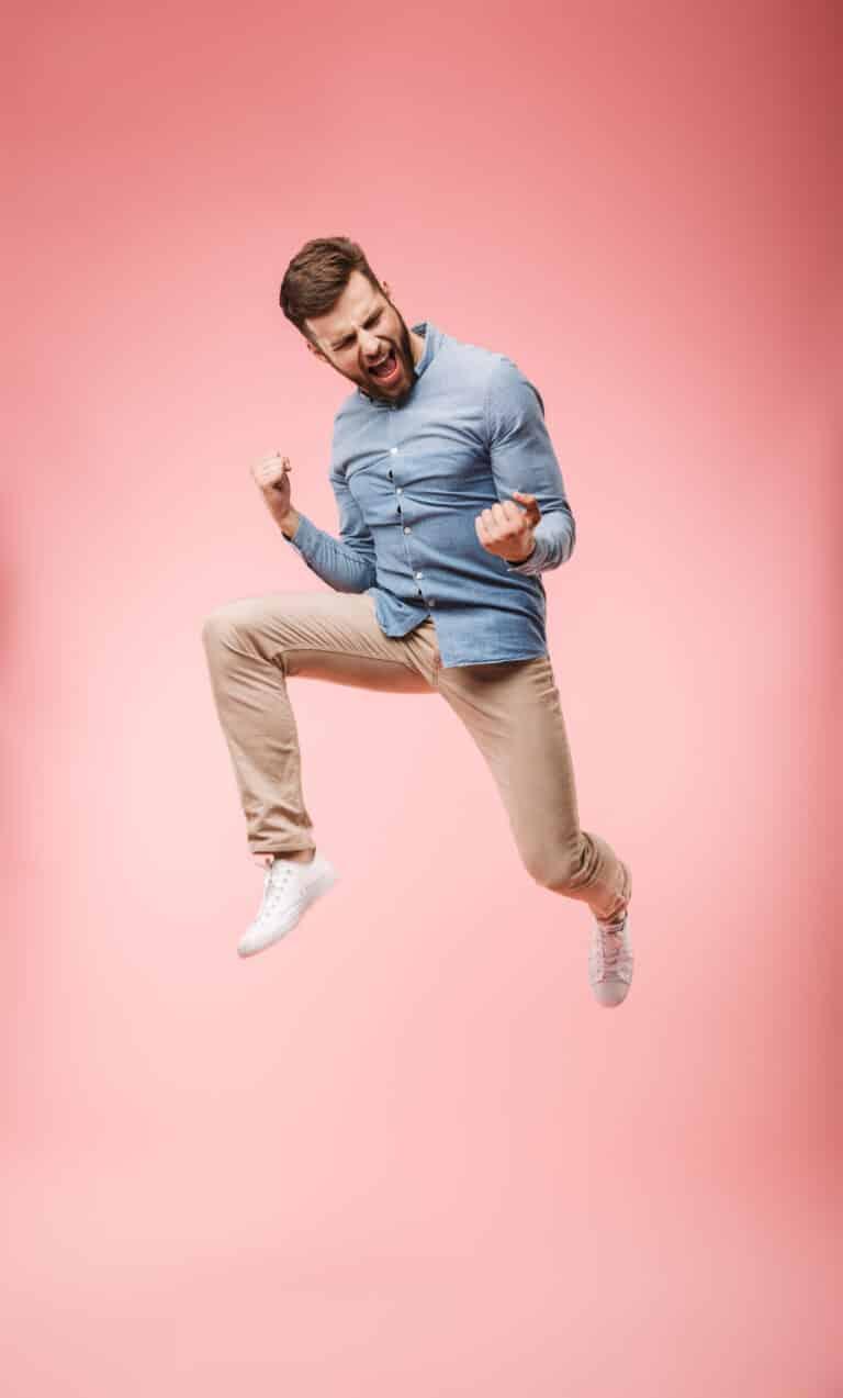 Un joven saltando en el aire por su transporte de auto rapido y feliz