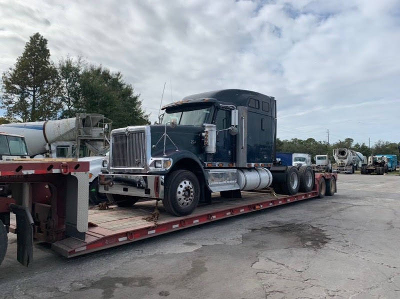 semi truck on trailer being transported across the country