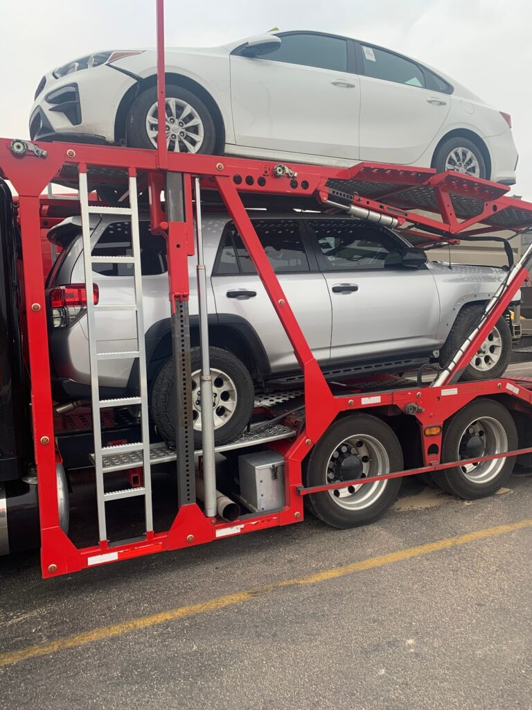 a red car transport trailer with two vehicles inside of it