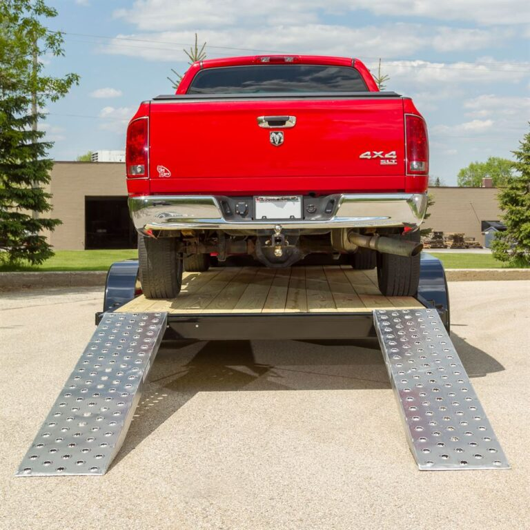 red dodge truck on ramps for car shipping