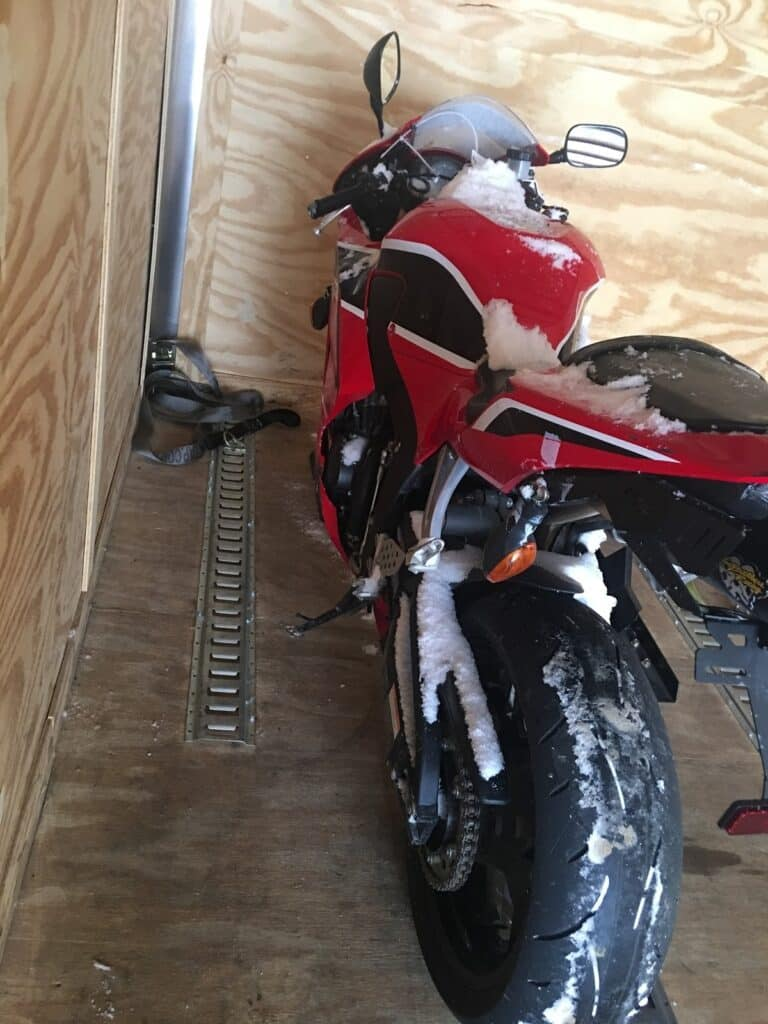 red motor cycle in transport trailer enclosed