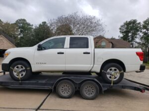 white nissan titan truck on transport trailer in residential driveway