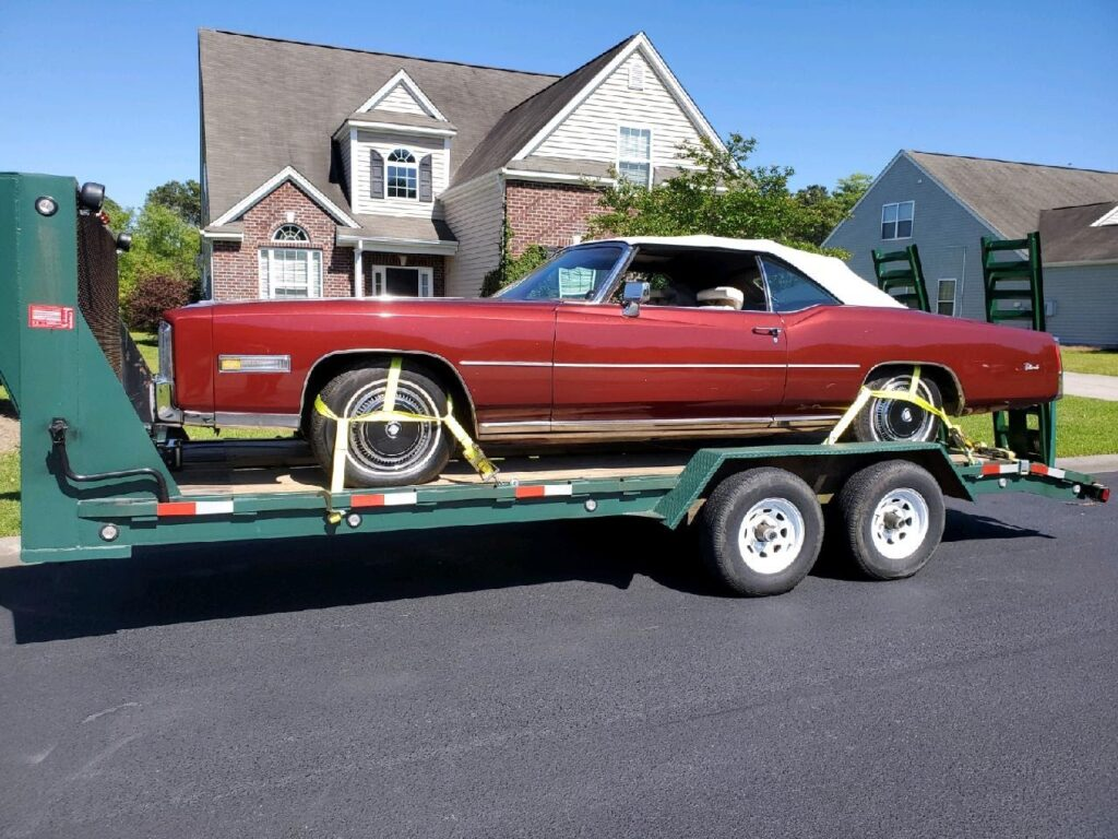 red 1976 el dorado classic on trailer for auto transport