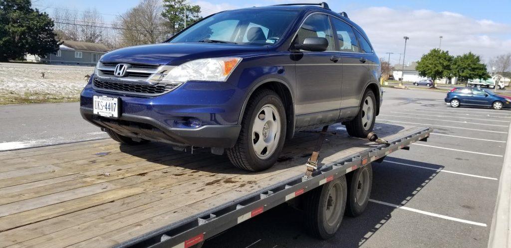 blue honda on auto transport trailer