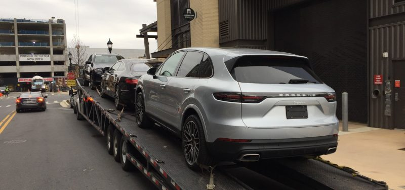 silver porsche suv on trailer for auto transport